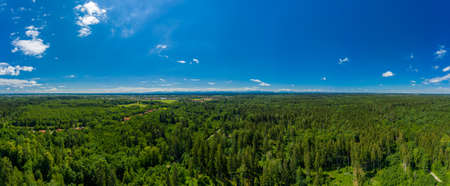 Beautiful panoramic aerial drone view over a green, fresh forest with a blue sky in summer - symbol for fresh air, health and photosynthesis environment. 写真素材 - 151209463