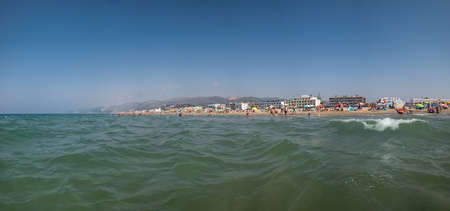 Holiday scene. View from the sea water and a wave at a travel destination with a beach at the horizon.