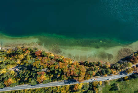 Top view drone shot of a lake with a colorful forest at autumn and a street in the lower section of the photo 写真素材 - 151176271