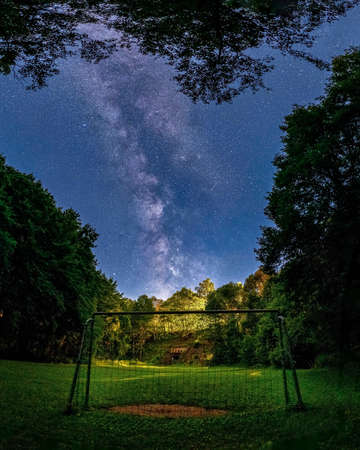 Night scene of a soccer goal on the field with milky way in the background.