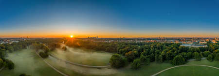 Wonderful sunrise over the English Garden of Munich, a green park in summer.