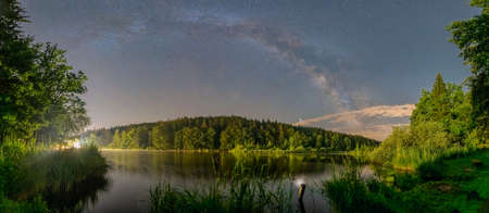The impressive millkyway galaxy captured with its panoramic arc. The big wood lake at night with sky with stars