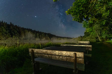 Focused milkyway at a star clear night in southern bavaria with a blurry park bench in foreground, idyllic moment in the night.
