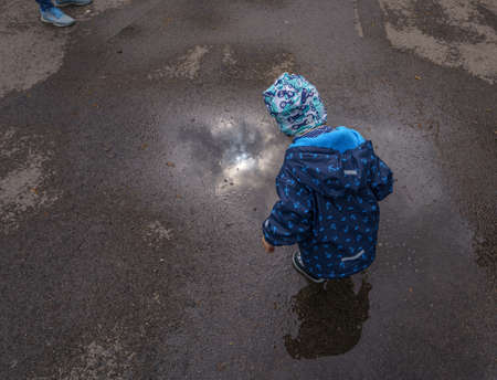 Little boy is watching a puddle after the rain is gone at a street.