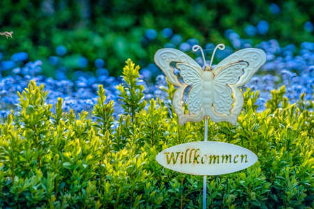 Plastic welcome sign in the garden with beautiful flowers in the background. 写真素材