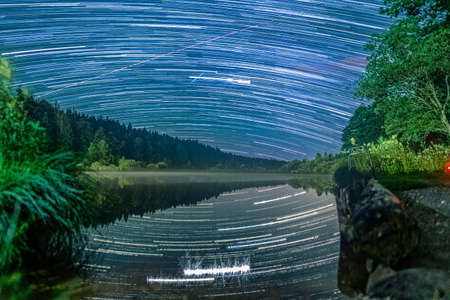 Long Exposure Startrails over an idyllic lake with star reflections in the water - wonderful star clear night. 写真素材 - 152191764