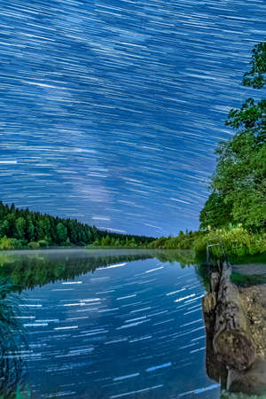 Long Exposure Star-trails over an idyllic lake with star reflections in the water - wonderful star clear night.