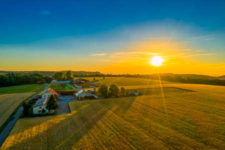 Glowing sunset aerial view at a farm house with a huge field in foreground.