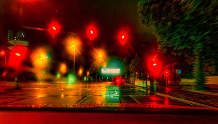 View through a front window of a car at the night stop at a colorful reflecting traffic light scenery in a town. 写真素材
