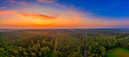 Aerial sunrise over a big forest with orange natural light, a wonderful morning in a panoramic view in southern germany.