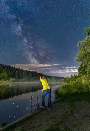 A man is pointing at the night sky milkyway, leaning at a banister in front of a lake. 報道画像