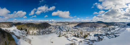 Idyllic town in a snowy winter, filmed from above, a drone shot in the Swabian Alb with hills and a part of a forest.