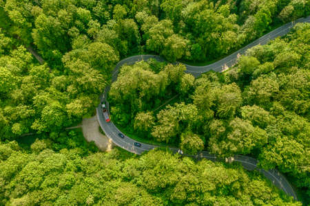 Aerial view of a green forest with a tractor on its leading through street slowing a row of cars behind it - traffic jam at a beautiful travel day