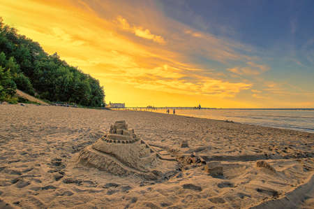 Beautiful holidays - a sand castle in the sunset at the sea, wonderful warm sandy beach in summer.