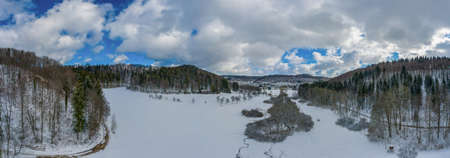 Idyllic winter pano in germany, swabian alb with snowy forest trees at the blue sky day. 写真素材