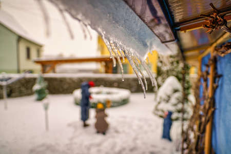 Icicles hanging from house roof in a garden with a blurry family in the background - typical winter scenery. 写真素材