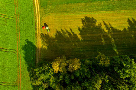 Aerial view of farm area with tractor standing in evening light