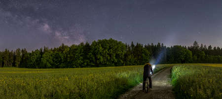 Panoramic photo of a man with his bike watching the beauty of the milkyway at the dark night sky at the countryside.