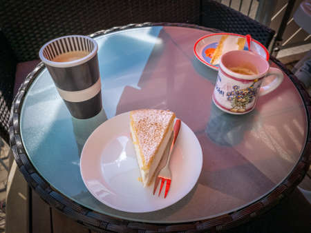 Tasty cheesecake on the table with cups of coffee for two people.