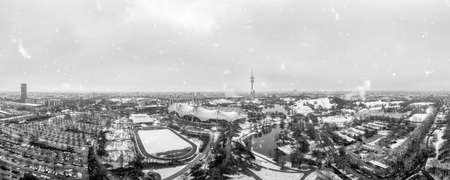 Snowflakes over Munich, the bavarian city in winter with the panoramic view over the Park, snow covered.