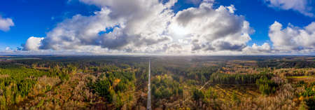Aerial panoramic view over a autumn forest with a blue sky and white clouds, the sun is shining in backlit.