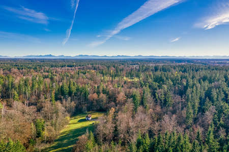Aerial view at a house in an idyllic property in the middle of a forest at autumn time with the alp mountains in the wide background.