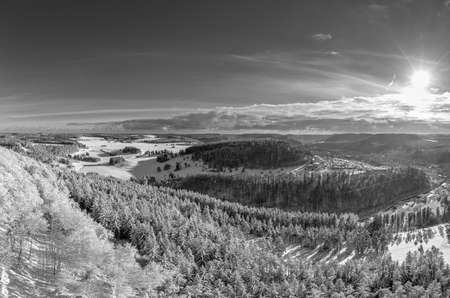 Snowy monochrome mountain winter landscape with sunny sky wide panorama.