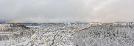 Panoramic wide white view over a winter cityscape with a town in the center 写真素材