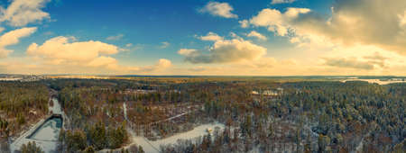 Winter fairytail view over a idyllic house in the middle of a white snow covered forest with green fir trees, aerial panoramic view of the winter season 写真素材