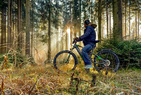 Mountain biker cyclist man is looking in the forest for the sunbeams coming through the trees, idyllic moment in the morning. 報道画像