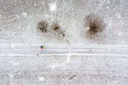 Aerial top down view at a colorful rainbow umbrella in the middle of a snow covered landscape at snowfall and some trees straight from above.