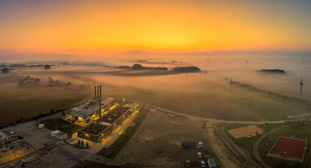 Aerial view of a foggy sunrise over a industrial area with a factory. Fog layered over a field next to a lake, bright early morning sunrise.