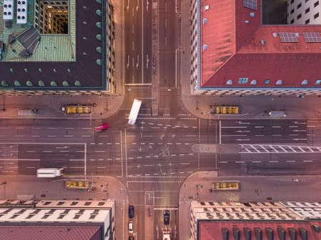 Aerial shot of an urban crossing road in a city with bend of cars from a top down view at the street between houses. 写真素材
