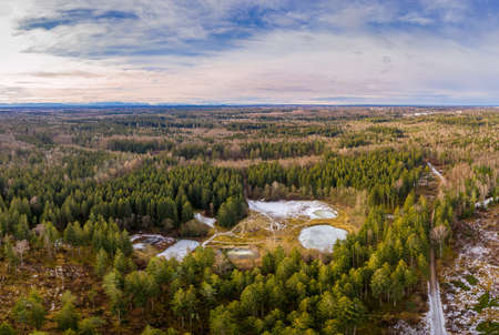 Aerial view of a small lakes inside a forest with conifer trees. Idyllic winter moment with the alp mountains in the background. Want you to have a walk here.