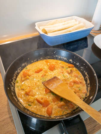 Delicious mail, a yellow curry at a pan is getting cooked with tomatoes and chicken meat.