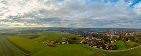 Foggy landscape from above as panoramic image of an idyllic bavarian village.