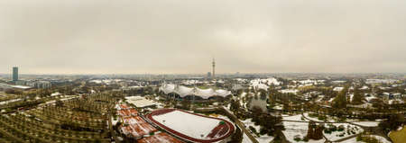 Panoramic view over Munich at the snowy wintertime, captured as an aerial from the beautiful park in the bavarian city.