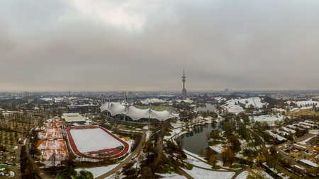 Winter in Munich, snow covered park in the heart of the bavarian metropole, a panoramic view at the  park with its tower and lake.