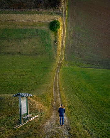 Droneception image showing a man watching along a long way between the field to a tree at the curved horizon. 写真素材