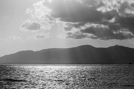 Wonderful sunlight in black and white - holiday photo with an awesome sunset over the sea, the warm sun is shining through the clouds.