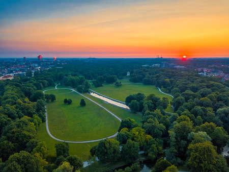 Wonderful total view over Munich Englischer Garten early at a summertime sunrise. The green public sightseeing hotspot filmed from above.