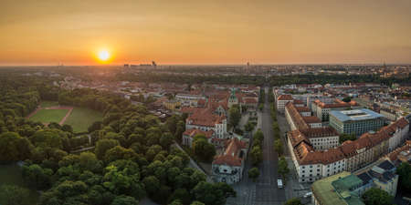 The wonderful view at Munich in bavaria from a drone, an panoramic aerial over a park, houses at the early summer sunrise in the center of the bavarian capital.