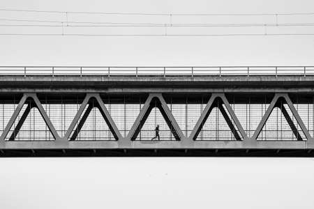 A man is jogging at the metal contrction of an iron bridge
