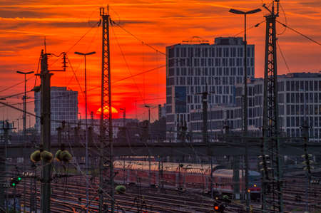 Impressive sunset over Munich and a business district in the background with the view over a railway with a driving train at the late evening.