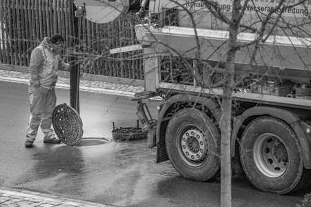 Sewer cleaning worker is looking into the manhole, standing behind his lorry with big wheels on the street in black and white.