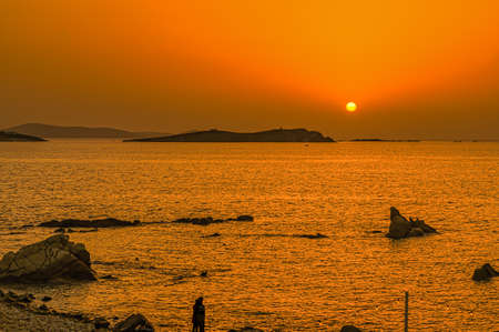 Silhouette of young couple at the sea holding each other watching the impressive sunset in their dreamy holidays.