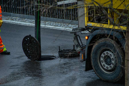 Drain cleaning worker is standing in front of an open manhole cover, doing his job at a rainy day on a street.