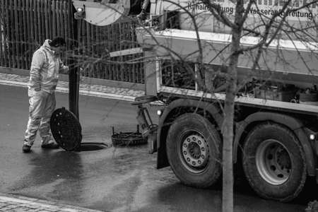 Sewer cleaning worker is looking into the manhole, standing behind his lorry with big wheels on the street in black and white in Oberhaching, 16th of march 2021, germany.