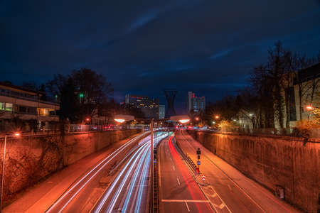 Munich, Germany - fast driving cars next to the central Effnerplatz in the bavarian capital at night with busy traffic as long exposure image, wonderful background.