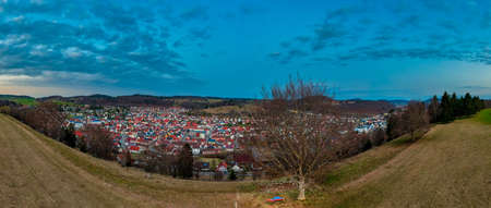 Wonderful view over the swabian alb and its city Albstadt as a panoramic drone shot at the evening atmophere with a man, sitting at a beautiful vista, enjoying the cityscape overview from a bench.